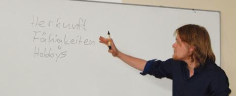 Rafael Rickfelder bewegt sich Richtung Tafel. Dort hebt er einen Stift auf und bearbeitet langsam eine Liste der verschiedenen menschlichen Qualitäten, die zur Beurteilung durch andere beitragen. Foto: Allison Meakem