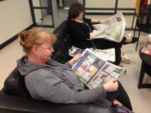 Viele Eltern, wie hier Marion Lange, suchen sich in der großen Schule einen komfortablen Platz aus und vertiefen sich in eine Zeitung, bis die Kinder fertig sind mit dem Unterricht. Foto: Phillip Reeves