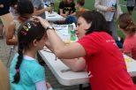 Eine GLC-Lehrerin malt Diamanten auf die Stirn eines der Kinder. Mit vielen verschiedenen Farben und Pinseln kann man vieles malen. Wie die langen Schlangen zeigen, lieben Kinder diese Malerei. Foto: Emma Lenz-Mann