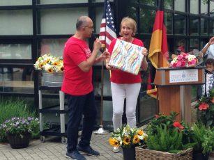 Vorstandsvorsitzender Dr. Al Zeitoun überreicht Schulleiterin Kerstin Hopkins ein besonderes Geschenk - eine Collage von Bildern von dem Botschaftsempfang zum 40-jährigen Jubiläum der GLC. Foto: Phillip Reeves